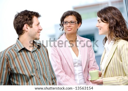 Happy young casual business people standing side by side in fornt of office window, talking and smiling.