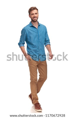 happy young casual man walking with hand in pocket on white background