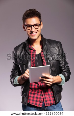 happy young casual man wearing leather jacket and working on a touchscreen tablet pad