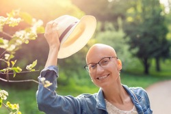 Happy young caucasian bald confident hipster woman take off hat and enjoying life after surviving breast cancer. Portrait of beautiful hairless girl smiling walking city park bright sunny backlit