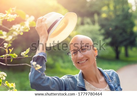 Happy young caucasian bald confident hipster woman take off hat and enjoying life after surviving breast cancer. Portrait of beautiful hairless girl smiling walking city park bright sunny backlit Stock photo ©
