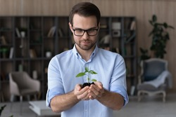 Happy young Caucasian businessman hold soil green plant think plan business project launch. Millennial male employee with sprout or seedling in hands, make investment. Development, growth concept.