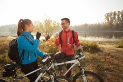 Happy young Caucasian couple eating energy bars, resting beside their bikes during early morning mountain bike ride along the lake shores in countryside