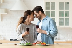 Happy young Caucasian couple enjoy romantic domestic date having tender moment in kitchen together, smiling loving millennial husband and wife drink wine cook at home celebrating wedding anniversary