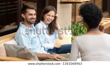 Happy young caucasian couple sitting on couch planning wedding listening to african counselor psychologist insurer planner consulting satisfied family clients talking laughing at meeting
