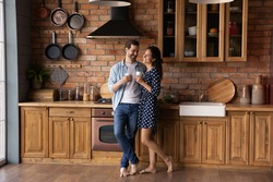 Happy young Caucasian couple stand in modern own kitchen at home drink coffee or tea enjoy sunny morning together. Smiling millennial man and woman celebrate relocation moving to new house.