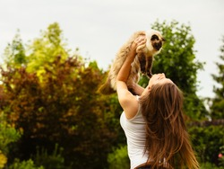 Happy young caucasian european female with white shirt and beautiful brown hair holding and loving a ragdoll birma cat in the air and playing on a garden with green trees