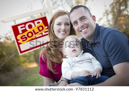 Happy Young Caucasian Family in Front of Sold Real Estate Sign.