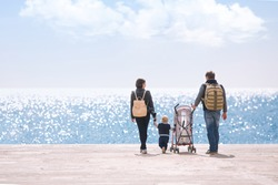 Happy young caucasian family with one year old son and stroller walking along wooden jetty on sunshine, back view. Happy family concept with copy space or text on left area