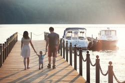 Happy young caucasian family with one year old son walking along wooden jetty on sunset. Happy family concept