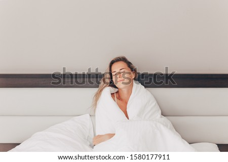 Happy young Caucasian girl lies on the bed and rests in a cozy bedroom. Mysterious woman rejoices on her long-awaited vacation. Rest Sleep Recovery Concept. Coyspace. Sweet home happy time