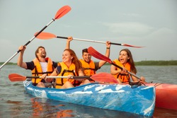 Happy young caucasian group of friends kayaking on river with sunset in the backgrounds. Having fun in leisure activity. Happy male and female model laughting on the kayak. Sport, relations concept.