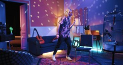 Happy young Caucasian handsome stylish man listening to music in headphones and dancing making rhythmic moves in living room in disco ball light in apartment, retro style, having fun, leisure concept