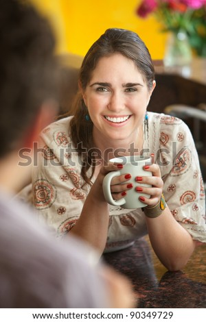 Happy young Caucasian lady with mug and friend