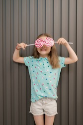 Happy young caucasian little girl kid with happy big sweet lollypops candy over her eyes on gray striped background