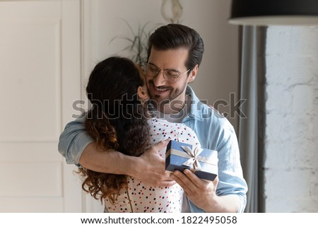 Happy young Caucasian man hug woman congratulate with anniversary present wrapped gift box. Smiling loving husband embrace wife greeting with birthday, make surprise for beloved. Relationship concept.