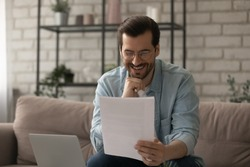 Happy young Caucasian man sit on couch at home read good news in postal paper letter, smiling millennial male in glasses get pleasant message or promotion offer in post paperwork correspondence