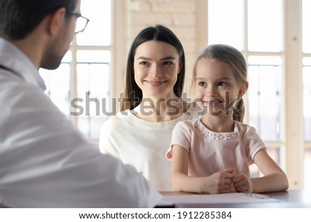 Happy young Caucasian mom and little 7s daughter have consultation with male doctor in private clinic. Smiling mother and small girl child talk speak with man GP or pediatrician. Childcare concept. Zdjęcia stock ©
