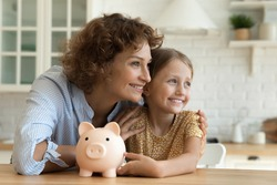 Happy young Caucasian mother and little daughter save money in piggybank dream think of wealth future. Smiling mom and small girl child feel economical provident make investment. Savings concept.