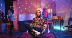 Happy young Caucasian stylish guy sitting in chair in living room in neon disco ball light, looking at camera and smiling while multi-ethnic friends dancing and moving behind having fun at party time