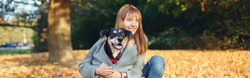 Happy young Caucasian woman hugging dog in park. Owner with pet on autumn fall day. Best friends having fun outdoor. Friendship of human with domestic animal. Web banner header.
