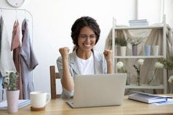 Happy young Caucasian woman in glasses sit at desk look at laptop screen triumph receive good news in email, excited female feel overjoyed euphoric win online lottery on computer, luck concept