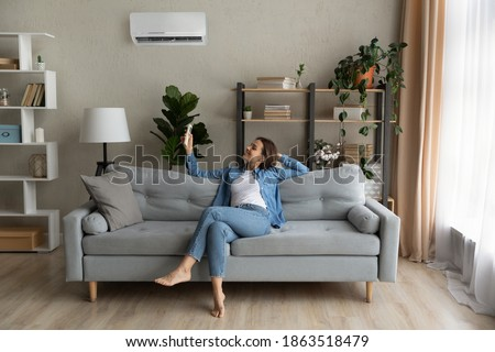 Happy young Caucasian woman relax on couch in living room turn on air conditioner with remote controller. Smiling female rest on sofa at home breathe fresh air from ac electronic condition device.