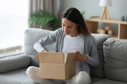 Happy young Caucasian woman sit on couch in living room unpack cardboard box with Internet order, smiling millennial girl open unwrap carton parcel at home, online shopping, good delivery concept