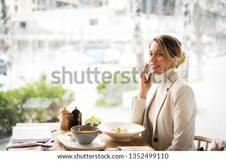 Happy young charming woman in white suite working on laptop while sitting alone in restaurant at business lunch, celebrating success