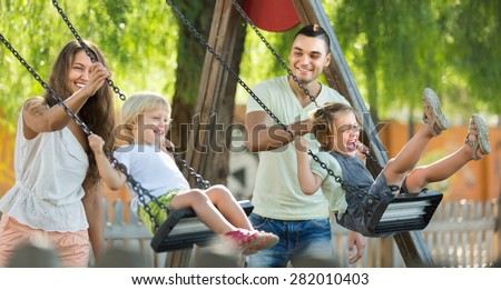 Happy young cheerful family of four at playground\'s swings. Focus on woman