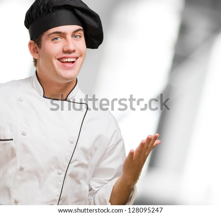 Happy Young Chef Gesturing against an abstract background