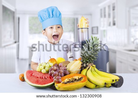 Happy young chef is making healthy fruit juice at home