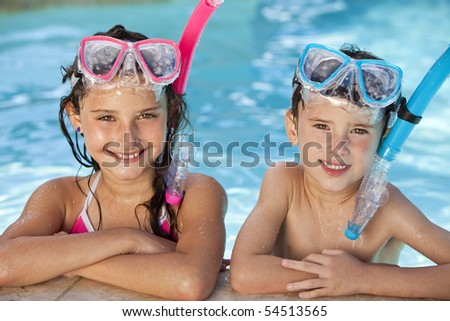 Happy young children, boy and girl, relaxing on the side of a swimming pool wearing blue and pink goggles and snorkel