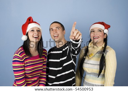 Happy young  Christmas  friends people with Santa hats  laughing together while the man pointing up somewhere towards the top right