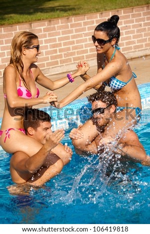 Happy young companionship having summer fun in swimming pool outdoor.