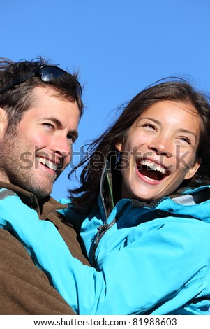 Happy young couple active outdoors. Smiling portrait of couple outside in jackets during hiking vacation. Asian woman model and Caucasian male model/
