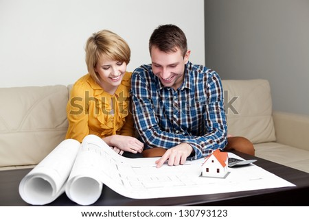 Happy young couple analyzing home blueprints.