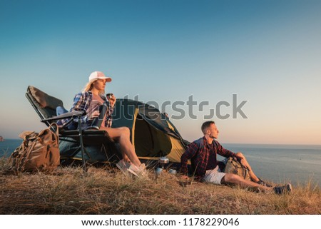 Happy young couple at campsite tent near seaside. Man and woman camp on summer outdoor adventure hiking trip in mountain. #1178229046