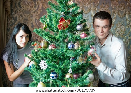 Happy young couple at Christmas. Happy young woman and man in domestic room on Christmas day.