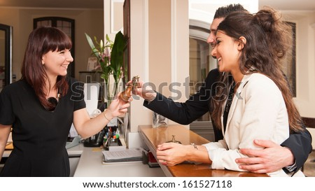 Happy Young Couple At Hotel Reception Receiving The Key Of The Room.