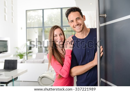 happy young couple at new house front door welcoming people  #337221989