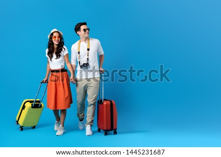 Happy young couple being ready to go for their holidays with colorful suitcases isolated on blue background with copy space