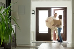 Happy young couple carrying cardboard boxes opening door entering inside modern own house, excited married family property owners moving in into new home, buying real estate, mortgage loan