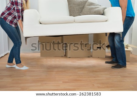 Happy Young Couple Carrying Couch In New Home #262381583