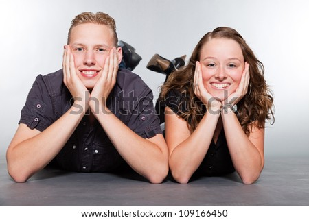 Happy young couple casual dressed. Studio shot isolated on grey background. Man with short blond hair. Woman long brown hair.