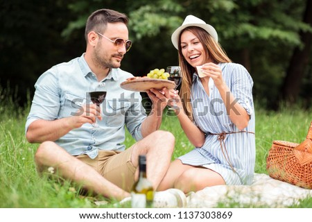 Happy young couple celebrating anniversary or birthday by having a romantic picnic in park. Eating cheese, grapes and drinking red wine. Love and dating, romance, lifestyle concept #1137303869