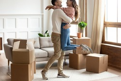 Happy young couple celebrating moving day in new apartment, loving husband holding wife, excited family hugging in living room, relocation into first new house, relocation and mortgage