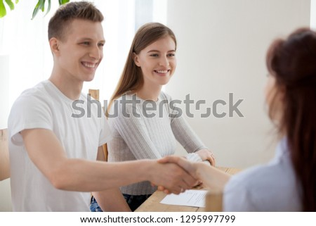 Happy young couple clients handshaking insurer bank worker advisor at meeting, smiling hr recruiters and applicant shaking hands greeting at job interview hiring making first impression, recruiting