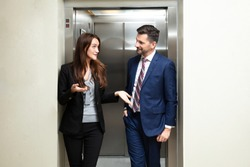 Happy Young Couple Coming Out From An Elevator