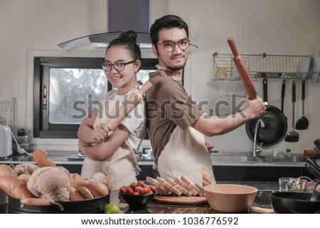 happy young Couple cooking in the kitchen, Asian couple activity in kitchen, with lots of fruit and bread, where the couple eating fruit - Shutterstock ID 1036776592